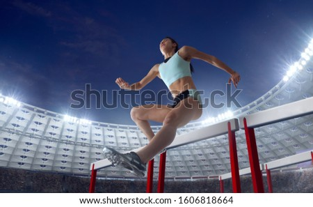 Athlete woman athlete jumps over the barrier at the running track in professional athletics stadium. #1606818664