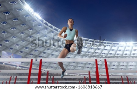 Athlete woman athlete jumps over the barrier at the running track in professional athletics stadium. #1606818667