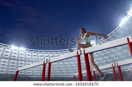 Athlete woman athlete jumps over the barrier at the running track in professional athletics stadium. #1606818670