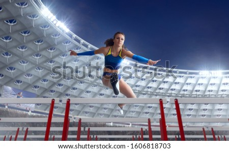Athlete woman athlete jumps over the barrier at the running track in professional athletics stadium. #1606818703