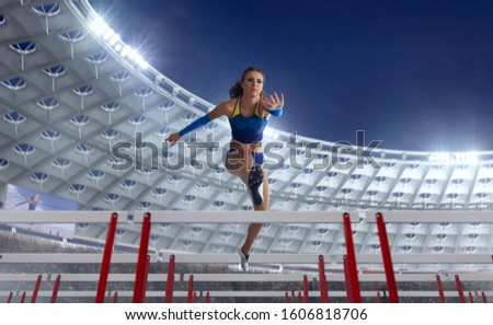 Athlete woman athlete jumps over the barrier at the running track in professional athletics stadium. #1606818706
