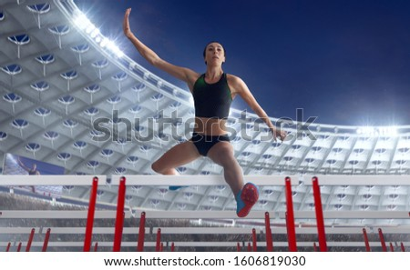 Athlete woman athlete jumps over the barrier at the running track in professional athletics stadium. #1606819030