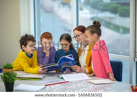 Learning English grammar. Children reading a book during their English class Royalty-Free Stock Photo #1606836502