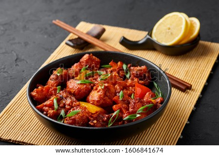 Fish Manchurian dry looks like Schezwan Fish in black bowl at dark slate background. Fish Manchurian - is indo chinese cuisine dish with deep fried salmon, bell peppers, sauce and onion. #1606841674