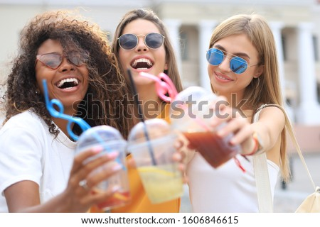 Three trendy cool hipster girls, friends drink cocktail in urban city background. #1606846615
