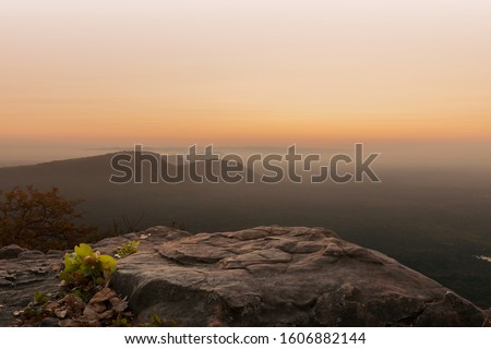 Cliff stone located part of the mountain rock on the top hill with mountain view at sun rise time. Royalty-Free Stock Photo #1606882144