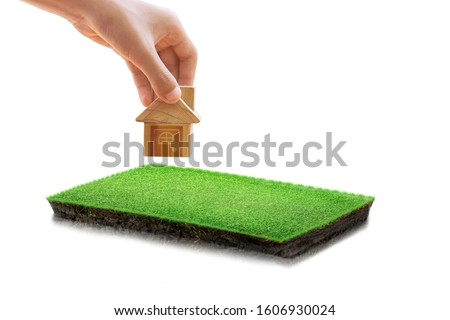 House symbol and, land plot for housing construction project.  round soil ground cross section with earth land and green grass, realistic rectangle cutaway terrain floor with rock isolated Royalty-Free Stock Photo #1606930024