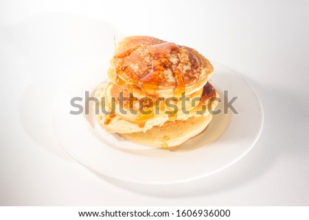 pancakes stacked on a white plate , The pancakes are topped with honey #1606936000