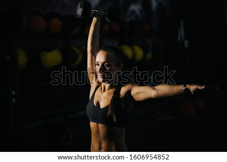 Sexy strong muscular female with perfect muscular body in black sportswear is lifting kettlebell overhead during weight training workout. Concept of healthy lifestyle and workouts in a modern dark gym #1606954852