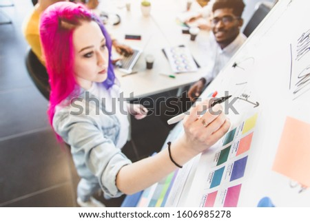 Group of multi ethnic executives discussing during a meeting. Business man and woman sitting around table at office and smiling. A team of young creative designers #1606985278