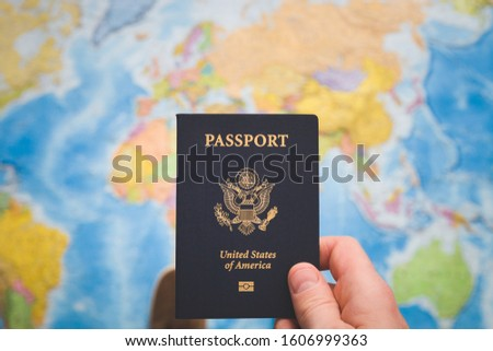 Top view of man holding usa passport on world map background. Passport control. A young man is preparing for a business trip or vacation. Traveling the world. #1606999363
