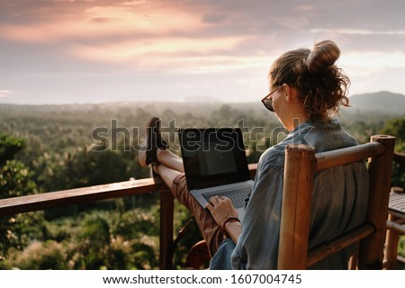 Young business woman working at the computer in cafe on the rock. Young girl downshifter working at a laptop at sunset or sunrise on the top of the mountain to the sea, working day. #1607004745