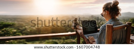 Young business woman working at the computer in cafe on the rock. Young girl downshifter working at a laptop at sunset or sunrise on the top of the mountain to the sea, working day. Royalty-Free Stock Photo #1607004748