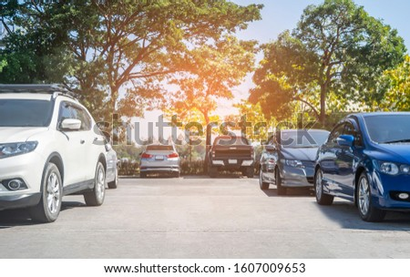 Cars parked in parking lot with trees background, empty space for car parking. Outdoor parking lot with green environment. nature travel transportation technology concept #1607009653