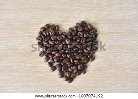 Coffee beans in heart shape. Heart shape made from roasted coffee beans on wood, top view #1607074192