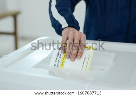 Person hand putting vote in a ballot box. Voters on election day.  Citizens casting their votes. People go to the polls. Presidential and parliamentary elections.  #1607087713