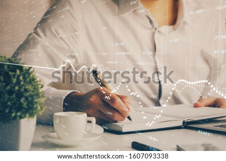 Double exposure of man's hands writing notes of stock market with forex chart. #1607093338
