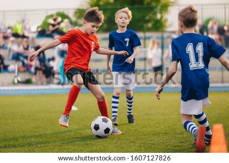 Young boys playing soccer game. Training and football match between youth soccer teams. Junior competition between players running and kicking soccer ball. Final game of football tournament for kids #1607127826