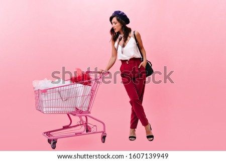 Girl with hat looks into cart and remembers whether she bought everything in store #1607139949