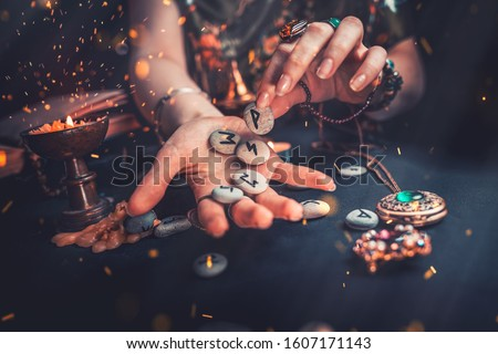 Astrology and esotericism. The witch puts the rune stones in his hand, standing next to the candle. Sparks of fire in the air. Dark background. Copy space Royalty-Free Stock Photo #1607171143