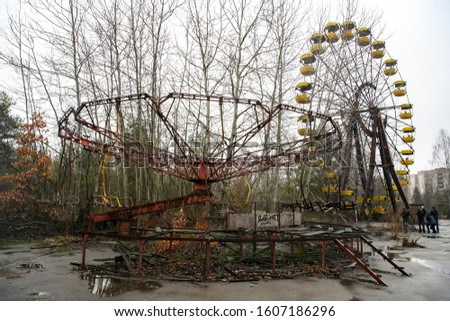 Abandoned amusement park in ghost town Prypiat. Overgrown trees and collapsing buildings in Priryat, Chornobyl exclusion zone. December 2019  #1607186296