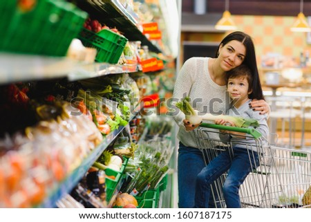 mother and her son buying fruits at a farmers market #1607187175