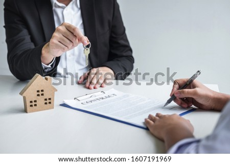 Estate agent giving house keys to client after signing agreement contract real estate with approved mortgage application form, concerning mortgage loan offer for and house insurance. #1607191969
