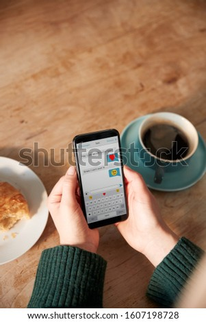 Close Up Of Woman Looking At Messages Arranging Romantic Date On Mobile Phone Messaging App In Cafe #1607198728