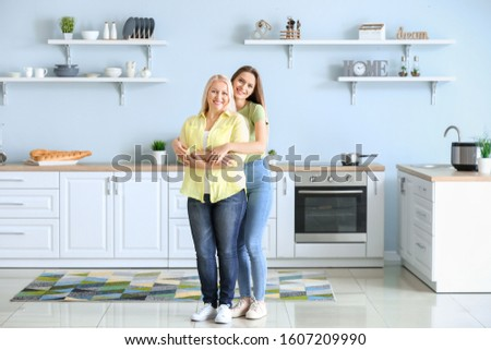 Mature woman and her adult daughter together in kitchen #1607209990