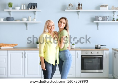 Mature woman and her adult daughter together in kitchen #1607209993
