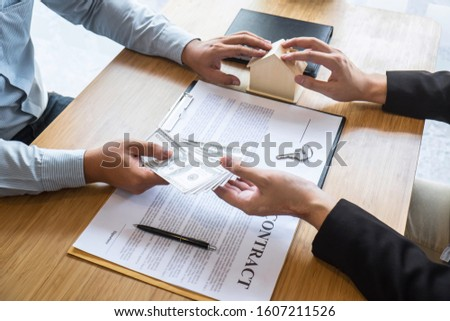 Real estate agent are presenting home loan and sending keys to customer after signing contract to buy house with approved property application form, Insurance Home concept. #1607211526