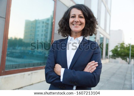 Happy cheerful female professional with folded arms standing near office building, looking ta camera, smiling. Middle aged business woman posing outside. Business portrait concept #1607213104