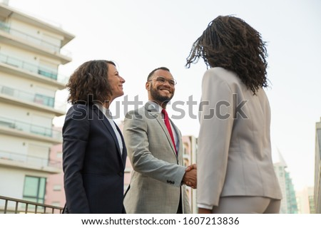 Multiethnic business partners meeting near office building. Business man and women shaking hands with each other outside in city. Collaboration concept #1607213836