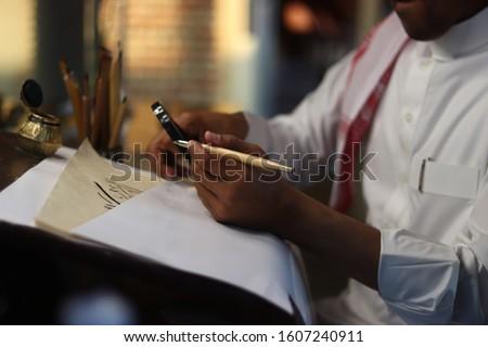 Skilled Arab Man doing Arabic Calligraphy