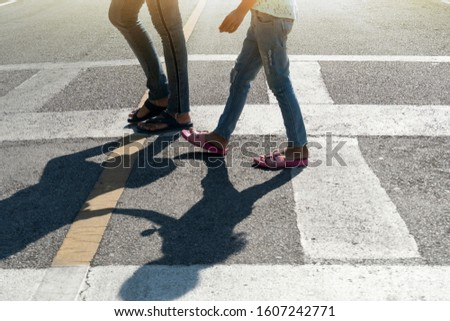 Mother and child's legs walk across the zebra crossing on an asphalt road. #1607242771