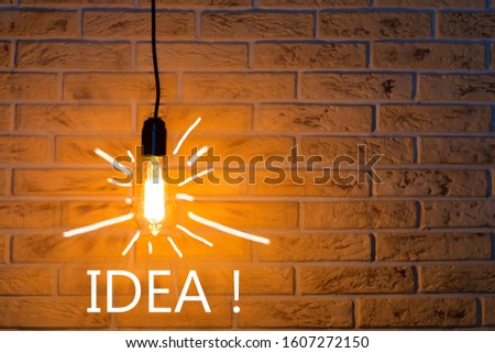 Vintage fashionable edison lamp on brick background with an inscription idea . Creative idea concept, designer lamp, modern interior item. Lighting, electricity, background with lamp. #1607272150