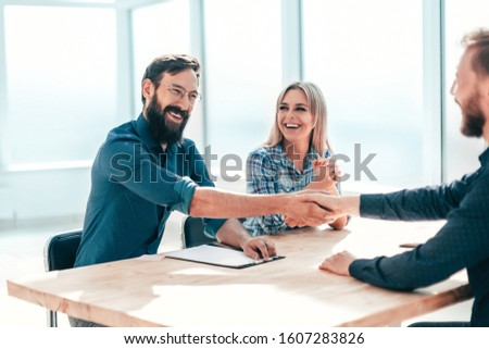 smiling young man answering employers ' questions during the interview #1607283826