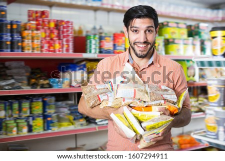 Portrait of smiling male who is standing with purchases in market #1607294911