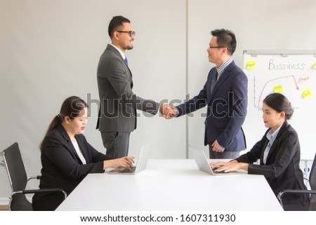 Business executives, executives, and company representatives are working together to sign a mutual friendly agreement. In front of them, there are secretary printing documents on the laptop. #1607311930