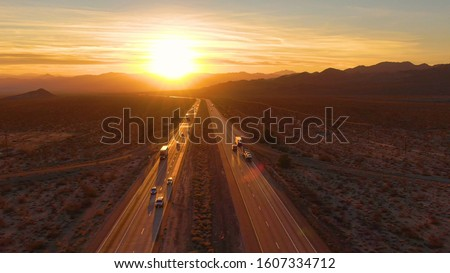 DRONE, SUN FLARE: Scenic shot of 18 wheeler trucks and cars crossing Mojave desert at dusk. Golden evening sun rays shine on the traffic moving up and down the straight freeway in rural California. Royalty-Free Stock Photo #1607334712