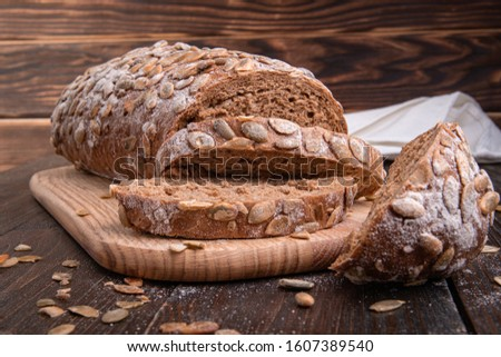 homemade grain bread on a wooden background with grains and seeds #1607389540