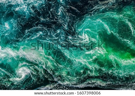 Abstract background. Waves of water of the river and the sea meet each other during high tide and low tide. Whirlpools of the maelstrom of Saltstraumen, Nordland, Norway #1607398006