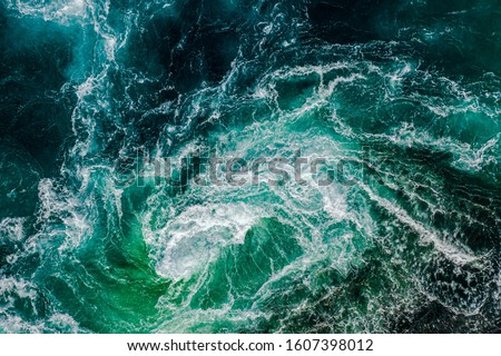 Abstract background. Waves of water of the river and the sea meet each other during high tide and low tide. Whirlpools of the maelstrom of Saltstraumen, Nordland, Norway Royalty-Free Stock Photo #1607398012