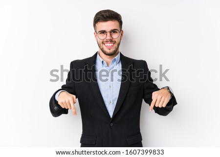 Young caucasian business man posing in a white background isolated Young caucasian business man points down with fingers, positive feeling. #1607399833