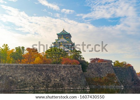 Osaka Castle building with colorful maple leaves or fall foliage in autumn season. Colorful trees, Osaka City, Japan. Architecture landscape background. Famous tourist attraction.