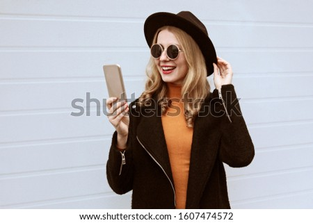 Stylish smiling young woman taking selfie picture by smartphone or video calling wearing black coat and round hat on city street over wall background