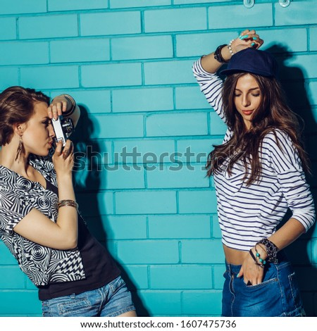 Lifestyle portrait of two beautiful best friends hipster girls wearing stylish bright outfits and denim shorts going crazy and having great time. Standing together near blue brick wall with photo.