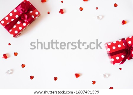The Background Of Valentine's Day. Gifts with bows, confetti, rhinestones, glass hearts on a light background. The Concept Of Valentine's Day. Flat lay, top view, copy space #1607491399