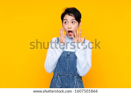 Young Asian girl in overalls over isolated yellow background with surprise facial expression #1607501866