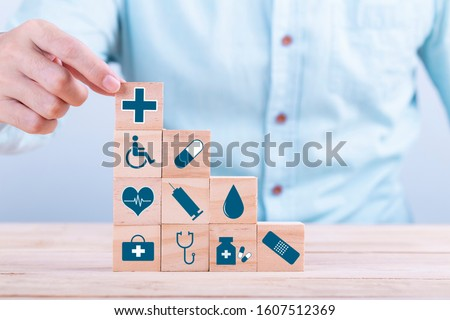 Hand chooses a emoticon icons healthcare medical symbol on wooden block , Healthcare and medical Insurance concept #1607512369